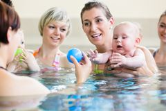 Behandla som ett barn och deras mammor på moder-och-barn-simning grupp arkivbild