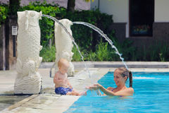 Behandla som ett barn och fostra att spela som är undervattens- med gyckel i simbassäng Royaltyfria Bilder