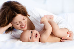 Behandla som ett barn och fostra hemma i säng Mom och barn royaltyfria foton