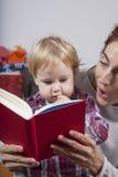 Behandla som ett barn och mamman som läser den röda boken Royaltyfria Bilder