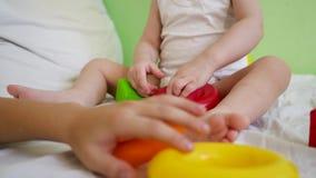 Behandla som ett barn och mamman som spelar med färgrik leksaker på sängen Barnlekar i rum på vit säng med röda och gröna kuber o stock video