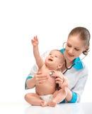 Behandla som ett barn och manipulera pediatriskt. doktorn lyssnar till hjärtan med s Fotografering för Bildbyråer