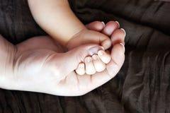 Behandla som ett barn och moderns hand Arkivfoton