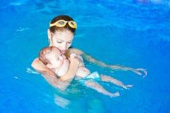 Behandla som ett barn och moher på simningkursen Royaltyfri Bild