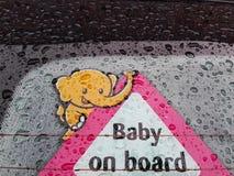 Behandla som ett barn ombord affischen på bilfönster royaltyfria bilder