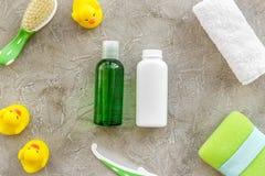Behandla som ett barn omsorg med den baduppsättningen, ankungar och handduken på bästa sikt för grå bakgrund Arkivfoto