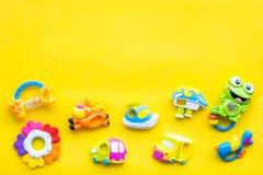 Behandla som ett barn omsorg med hantverkleksaker för nyfött rattle Gult utrymme för kopia för bästa sikt för bakgrund royaltyfri bild