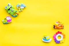 Behandla som ett barn omsorg med hantverkleksaker för nyfött rattle Gult utrymme för kopia för bästa sikt för bakgrund royaltyfria foton