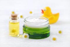 Behandla som ett barn omsorgprodukter, naturlig kräm, olje- och nya kamomillblommor för massage royaltyfria foton