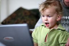 Behandla som ett barn på en dator arkivbild