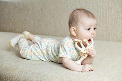 Behandla som ett barn palying med leksakgiraffet Arkivfoto