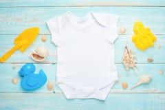 Behandla som ett barn plan lekmanna- vit för modellen bodysuitskjortan på en blå lantlig träbakgrund med ett nautiskt tema, snäck royaltyfri foto