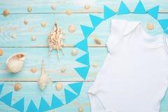 Behandla som ett barn plan lekmanna- vit för modellen bodysuitskjortan på en blå lantlig träbakgrund med ett nautiskt tema, snäck fotografering för bildbyråer