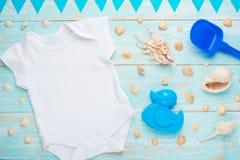 Behandla som ett barn plan lekmanna- vit för modellen bodysuitskjortan på en blå lantlig träbakgrund med ett nautiskt tema, snäck royaltyfria foton