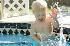 Behandla som ett barn plaskande vatten i trädgårdsimbassäng Arkivfoto