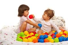 Behandla som ett barn pojke- och litet barnflickan med bollar royaltyfri foto