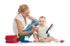 Behandla som ett barn pojke- och moderlek samman med leksaker Arkivfoto
