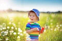 Behandla som ett barn pojkeanseendet i gräs på fiealden med maskrosor Royaltyfri Foto