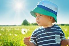 Behandla som ett barn pojkeanseendet i gräs på fiealden med maskrosor Arkivbilder