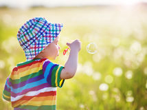 Behandla som ett barn pojkeanseendet i gräs på fiealden med maskrosor Royaltyfria Foton