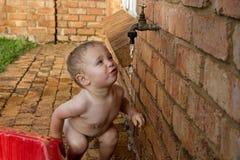Behandla som ett barn pojkedricksvatten från ett klapp Arkivfoto