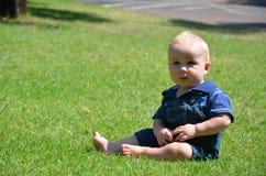 behandla som ett barn pojkegrässitting royaltyfri fotografi