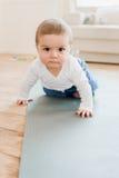 Behandla som ett barn pojkekrypningen på yoga som är matt med ilsket uttryck Fotografering för Bildbyråer