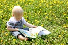 Behandla som ett barn pojkeläseboken i maskrosor Royaltyfri Bild