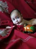 Behandla som ett barn pojkelögner på den indisk silver broderade mörker-körsbäret sjalen Royaltyfri Foto