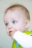 Behandla som ett barn pojken äter, medan sitta på en behandla som ett barnstol Arkivfoto
