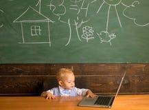 Behandla som ett barn pojken använder digitalt tillträde i datorgrupp Framkallande digital läs-och skrivkunnighetexpertis med nät arkivfoton