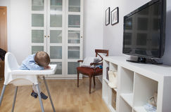 Behandla som ett barn pojken avverkar sovande på hans highchair Arkivbilder