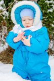 Behandla som ett barn pojken som förvånas med första snöinnehavsnö på hans hand Royaltyfri Bild