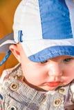 Behandla som ett barn pojken håller ögonen på något på jordningen Arkivbild