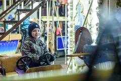 Behandla som ett barn pojken som har gyckel i en karusell Fotografering för Bildbyråer