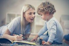 Behandla som ett barn pojken har lek med modern i vardagsrum Royaltyfri Fotografi