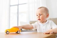 Behandla som ett barn pojken som hemma spelar med leksakbilen royaltyfri bild
