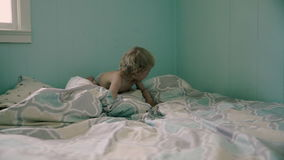 Behandla som ett barn pojken hoppar i sängen Royaltyfri Foto