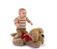 Behandla som ett barn pojken hoppar på flott hund Royaltyfria Bilder