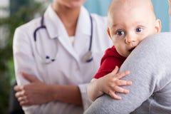 Behandla som ett barn pojken i armarna av modern på doktorns kontor Royaltyfria Foton