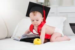 Behandla som ett barn pojken i avläggande av examenlocket som poserar med äpplet och den stora boken Fotografering för Bildbyråer