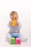 Behandla som ett barn pojken i blåttpyjamas som leker med, färgar kvarter arkivfoto