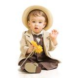 Behandla som ett barn pojken i dräkt med blomman. Tappningbarn Arkivfoton