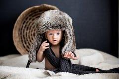 Behandla som ett barn pojken i en pälsvinterhatt Arkivbild