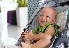 Behandla som ett barn pojken i en sittvagn Arkivfoto