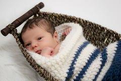 Behandla som ett barn pojken i en vide- korg Royaltyfri Foto