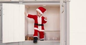 Behandla som ett barn pojken i jultomten som dräkten öppnar garderoben från inre arkivfilmer