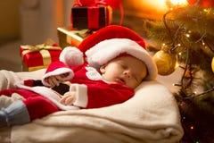 Behandla som ett barn pojken i jultomtendräkt som sover på spisen bredvid Christma Royaltyfria Bilder