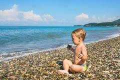 Behandla som ett barn pojken i lotusblomma poserar på stranden Arkivbild