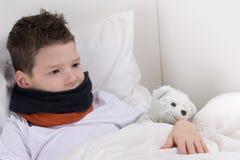 Behandla som ett barn pojken i säng, med en öm hals, återställer arkivbild